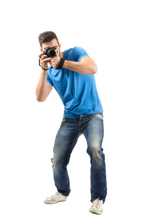 bend over: Bend or lean young man taking photo with dslr looking at camera. Full body length portrait isolated over white background.