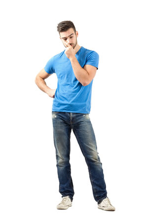 man confused: Young worried man thinking looking down. Full body length portrait isolated over white background. Stock Photo