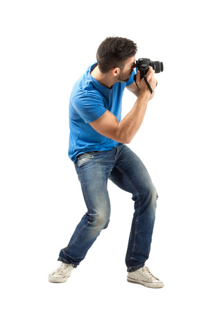 Bend young man taking photo with digital camera side view. Full body length portrait isolated over white background.
