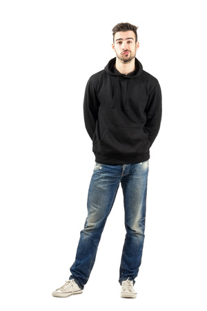 jeans: Confused young man in hoodie with hands on back. Full body length portrait isolated over white background. Stock Photo
