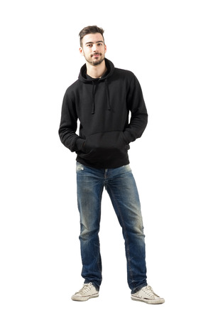 Young man in hoodie with hands in pockets smiling at camera. Full body length portrait isolated over white background.