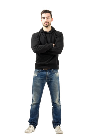 Young man in hoodie with crossed arms looking at camera. Full body length portrait isolated over white background.