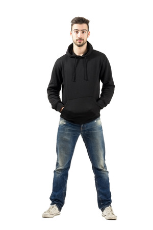 Young confident man in hood with hands in pocket looking at camera. Full body length portrait isolated over white background.