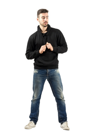 Young man holding hoodie strings looking down. Full body length portrait isolated over white background. photo
