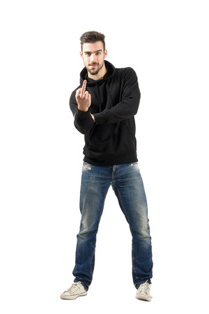 Rude young man in hoodie showing middle finger gesture. Full body length portrait isolated over white background. photo