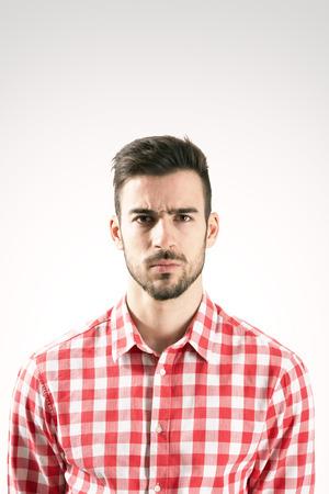 hombre con barba: Retrato de hombre con barba grave ofendido mirando a la cámara sobre fondo gris Foto de archivo