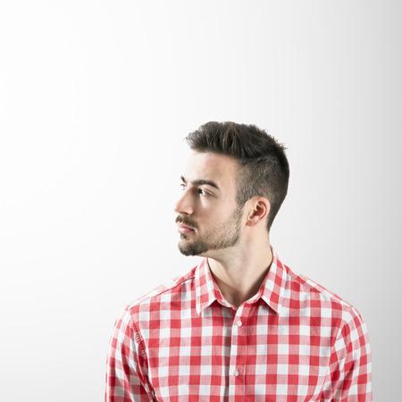 expresiones faciales: Perfil del hombre barbudo joven serio que mira lejos sobre fondo gris.