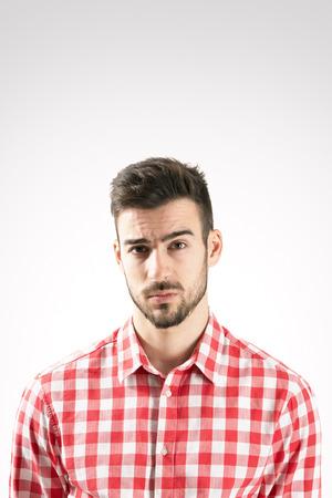 desconfianza: Retrato del hombre barbudo joven escéptico mirando a la cámara sobre fondo gris.