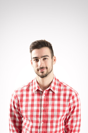 Portrait of smiling young bearded man looking at camera over gray background Stock Photo