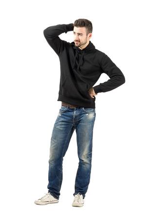 Durchdachter junger Mann Wegschauen auf Abstand. Ganzkörperansicht Portrait isoliert auf weißem Hintergrund.