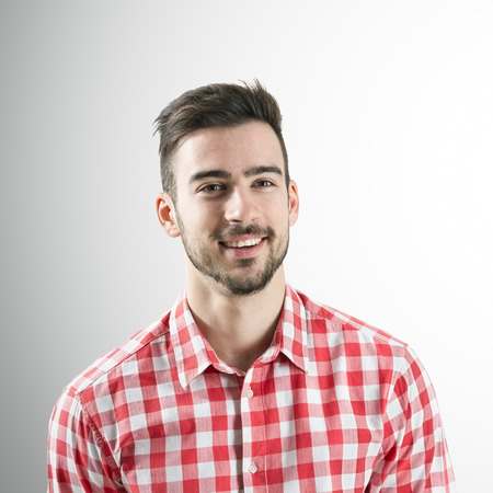 studio portrait: Portrait of spontaneous smiling positive young bearded man over gray background. Stock Photo