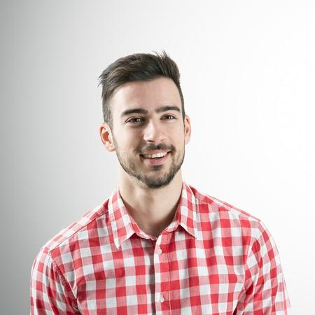hombre con barba: Retrato de hombre con barba espontánea sonrisa positivo jóvenes sobre fondo gris. Foto de archivo