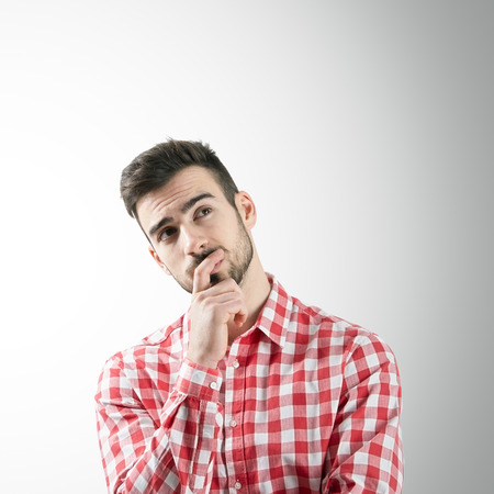 Portrait of bearded thinking young man looking up over gray background. Stockfoto