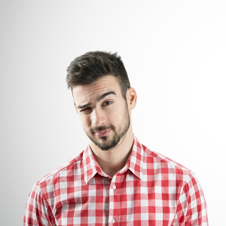 man close up: Portrait of young bearded man winking with his right eye over gray background. Stock Photo