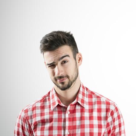 Portret van een jonge man met een baard knipogen met zijn rechteroog over grijze achtergrond. Stockfoto - 34341408