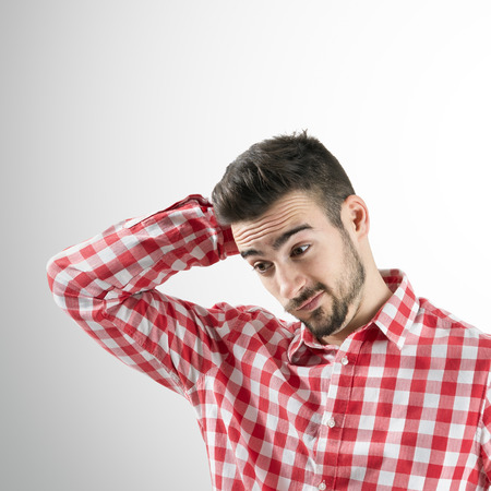 Portrait of confused young bearded man looking down. Desaturated over retro background with shadow