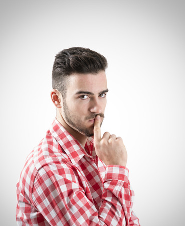 cautious: Portrait of pensive young bearded man looking at camera. Desaturated over retro background with vignette. Stock Photo