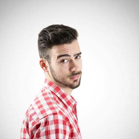 funny hair: Portrait of cynical bearded man looking at camera. Desaturated over retro background with vignette. Stock Photo