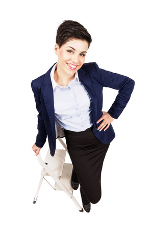 Young business woman beauty smiling on the construction ladder. High angle view wide lens full body length portrait isolated over white background. photo