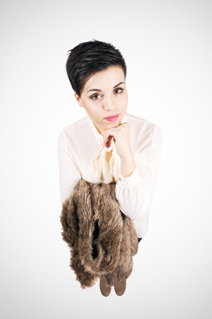 Young short hair fashion model holding fur jacket looking at camera. Retro style.  High angle view wide lens full body length portrait over vignette background. photo