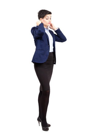 formal dressing: Young cute business woman putting on formal clothes.  Full body length portrait isolated over white background. Stock Photo