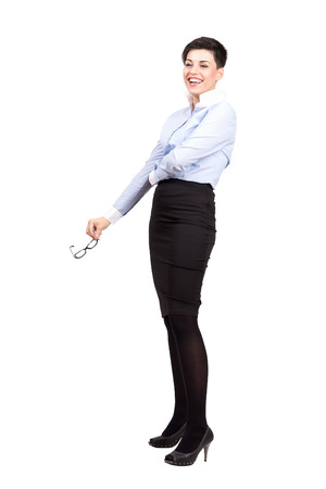 spontaneous expression: Young business woman laughing spontaneously holding eye glasses.  Full body length portrait isolated over white background. Stock Photo