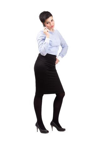 falda corta: Señora bastante joven de negocios hablando por el teléfono móvil. Cuerpo completo retrato de cuerpo entero aisladas sobre fondo blanco.