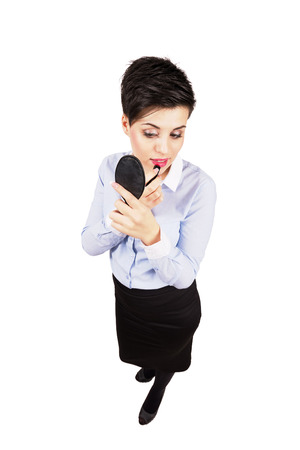full length mirror: Young businesswoman applying lipstick looking on hand mirror. High angle view wide lens full body length portrait isolated over white background
