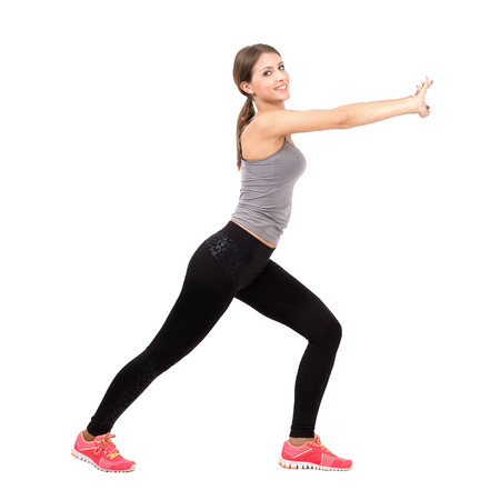 Side view of young beautiful slim sporty woman stretching and exercising. Full body length portrait isolated over white background. photo