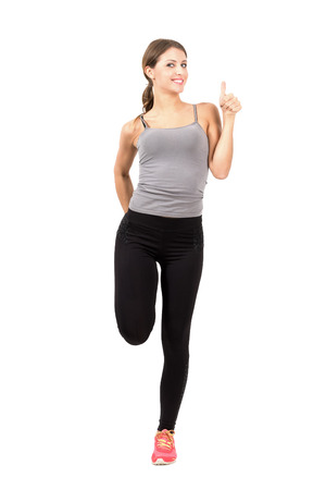 Young sporty woman stretching leg with thumbs up gesture.  Full body length portrait isolated over white background.