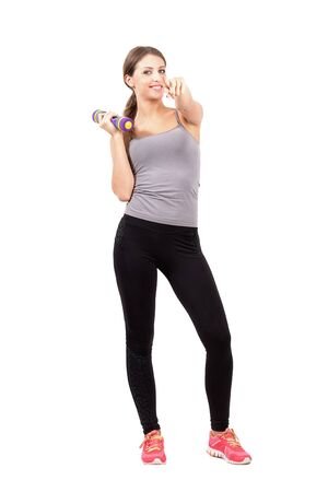 to beckon: Young sporty fitness woman holding dumbbell pointing at you. Full body length portrait isolated over white background. Stock Photo