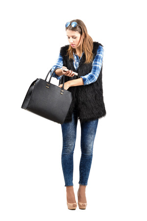 woman searching: Young trendy woman searching for something in her handbag. Full body length portrait isolated over white background