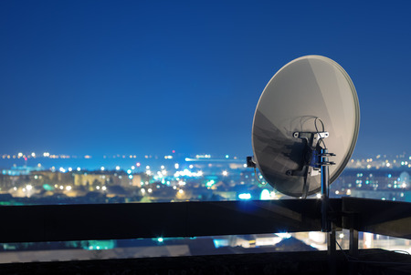 Satellite dish antenna on top of the building in urban area at night.