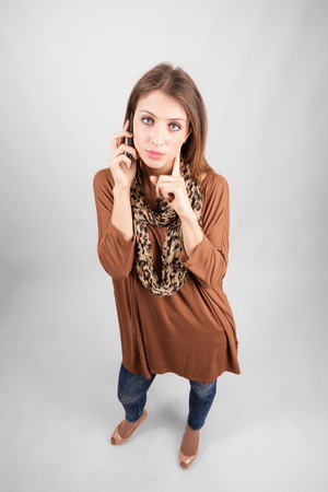 blue eye: Pensive blue eye beauty talking on the phone looking at camera. High angle view wide lens full body length portrait.