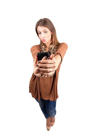 Splendida presa bellezza selfie trasmette bacio dell'aria. Alto angolo di vista l'obiettivo largo corpo pieno lunghezza ritratto isolato su sfondo bianco Archivio Fotografico