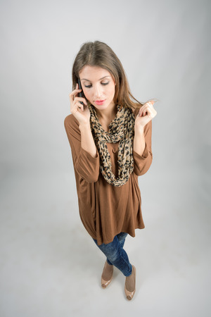 Pensive concerned beauty on the cellphone looking down. High angle view wide lens full body length portrait. photo