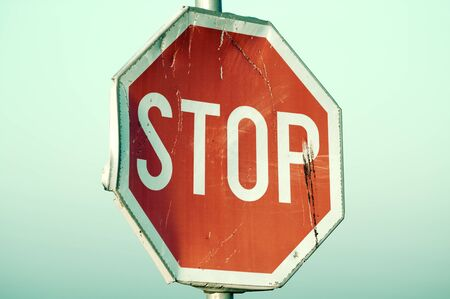 desaturated colors: Old rusty stop sign in retro paste color filter