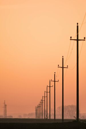 bare wire: Old retro telephone poles in the field at sunset