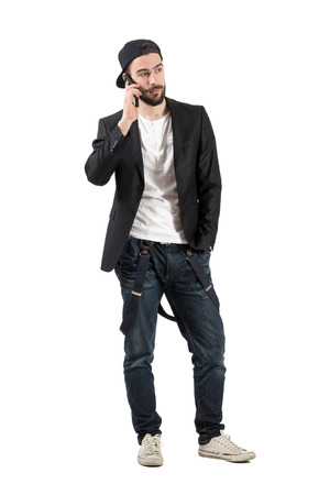 Serious young man talking on the cellphone wearing hat backwards. Full body length portrait isolated over white background.