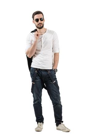modelos hombres: Modelo de joven y guapo de moda masculina posando con chaqueta sobre el hombro. Carrocer�a completa longitud retrato aislado sobre fondo blanco. Foto de archivo