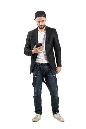 backward: Young guy in unusual clothes holding cellphone. Full body length portrait isolated over white background. Stock Photo