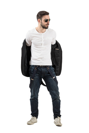 taking off: Handsome young man taking off jacket. Full body length portrait isolated over white background. Stock Photo