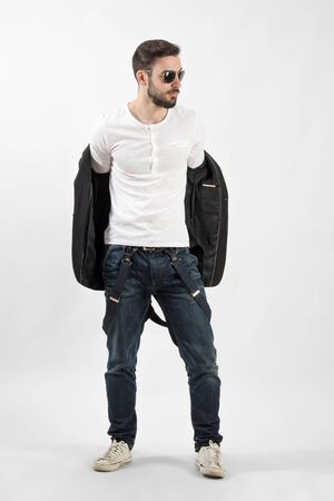 Young handsome fashion model putting on jacket. Full body length portrait over gray background. photo