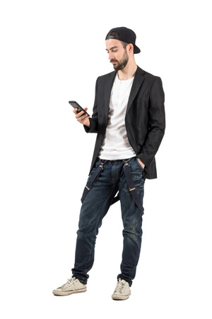 Young bearded man with backward hat using mobile phone device. Full body length portrait isolated over white background.