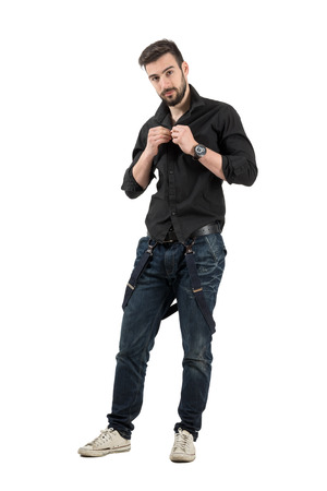 Handsome young fashion model buttoning black shirt.  Full body length portrait isolated over white background. photo