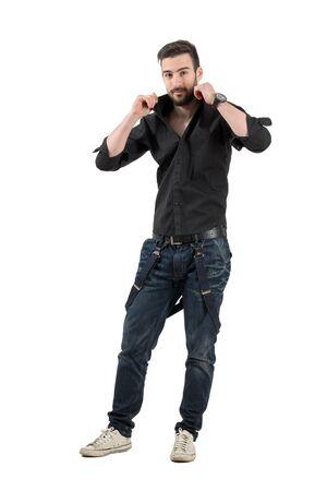 levantandose: Joven barbudo hermoso que ajusta el cuello de su camisa negro. Carrocería completa longitud retrato aislado sobre fondo blanco. Foto de archivo