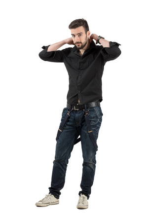 Young handsome male putting on clothes.  Full body length portrait isolated over white background. photo