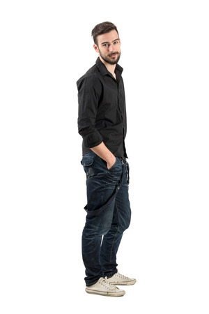man side view: Relaxed young man side view looking at camera. Full body length portrait isolated over white background.