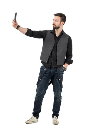 fashion photography: Trendy young man taking selfie photo with his mobile phone. Full body length portrait isolated over white background.