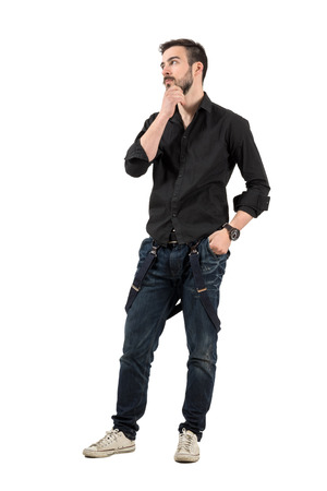 rolled up sleeves: Young cool trendy man touching his beard looking away. Full body length portrait isolated over white background.